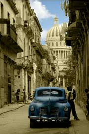 A photograph of a streetscape in Havana, Cuba, with El Capitolio (the National Capitol Building) in the background. By Omar Valenti.