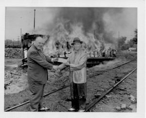James Towley Presenting check to Fred Ossanna with a burning streetcar behind them. Ossanna, then the head of the Twin City Rapid Transit Company, accepted bribes from Standard Oil and General Motors to shut down the streetcar system; he was eventually convicted of mail fraud and sentenced to four years in prison.