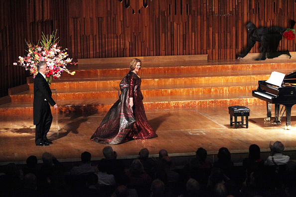 An unidentified Fleming fan (right, above piano) emerges from concealment to throw a bouquet of flowers to Ms. Fleming as she returns to the stage for a standing ovation. Read the review.