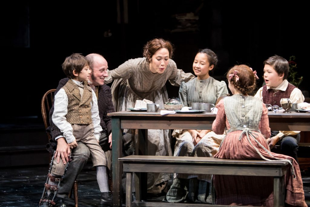 Sander Huynh-Weiss (Tiny Tim), Kris L. Nelson (Bob Cratchit), Meghan Kreidler (Mrs. Cratchit), Louisa Darr (Martha Cratchit), Mabel Weismann (Belinda Cratchit) and William Nida (Peter Cratchit) in the Guthrie Theater's A Christmas Carol. Photo by Dan Norman.