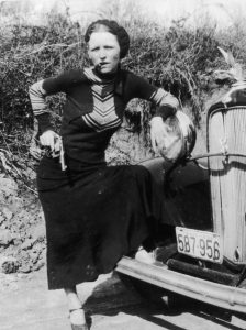A photo of Bonnie Elizabeth Parker mugging for the camera with a revolver and a cigar. This photo, part of a set recovered from a gang camera and published by newspapers across the United States - the early 20th century version of going viral.